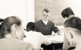 Professor watching as student write off on exams royalty free stock images