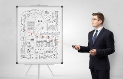 Professor on whiteboard teaching economy. Professor with laser pointer teaching business theories royalty free stock image