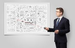 Professor on whiteboard teaching economy. Professor with laser pointer teaching business theories royalty free stock photo