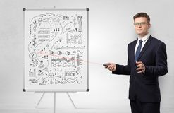 Professor on whiteboard teaching economy. Professor with laser pointer teaching business theories n stock images