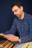 Professor at work. Working with very old books and taking notes stock photography