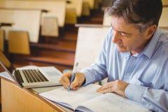 Professor writing in book at desk Stock Photo