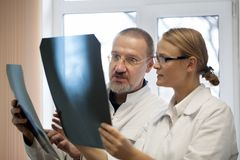 Professor and young doctor comparing x-rays Royalty Free Stock Image
