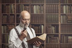 Professore accademico nella biblioteca che tiene un libro fotografia stock