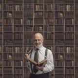Professore accademico nella biblioteca che tiene un libro immagini stock