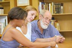 Professore anziano con il gruppo multirazziale che studia nella libreria Fotografia Stock Libera da Diritti