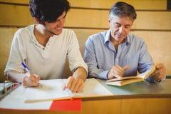 Professore che assiste uno studente con il suo studio Immagini Stock Libere da Diritti