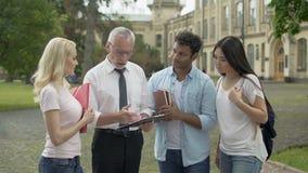 Professore che dà le assegnazioni al gruppo di studenti multi-etnici, istruzione video d archivio