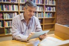 Professore che si siede allo scrittorio facendo uso della compressa digitale Immagini Stock Libere da Diritti