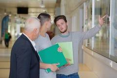 Professore con il taccuino che parla con studente in corridoio Fotografia Stock Libera da Diritti