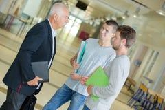 Professore con il taccuino che parla con studenti in corridoio immagine stock libera da diritti
