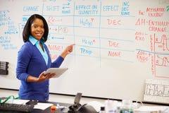 Professore di scienze Standing At Whiteboard con la compressa di Digital immagini stock