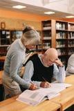 Professore di seconda fascia che aiuta un uomo anziano nella classe dell'università fotografia stock