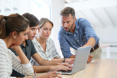 Professore e studenti che lavorano al computer portatile Immagine Stock Libera da Diritti