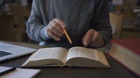 Professore maschio anziano del biologo sta esaminando il libro che si siede alla tavola in biblioteca universitaria video d archivio