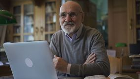 Professore maschio del biologo sta posando la seduta alla tavola con il computer portatile nella biblioteca di istituto universit archivi video