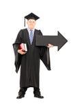 Professore maschio dell'istituto universitario che tiene grande freccia nera che indica destra Fotografie Stock Libere da Diritti
