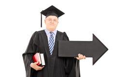 Professore maschio dell'istituto universitario che tiene grande freccia nera che indica destra Immagine Stock