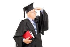 Professore maschio dell'istituto universitario nello sguardo dell'abito di graduazione Fotografie Stock