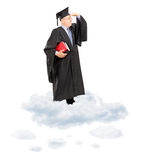 Professore maturo dell'istituto universitario in abito di graduazione che sta sulla nuvola Immagine Stock