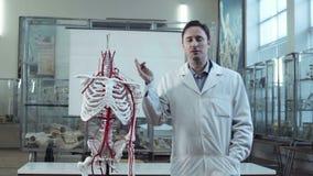Professore medico nella classe di anatomia con lo scheletro archivi video