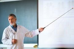 Professore senior di chimica che dà una conferenza Fotografie Stock