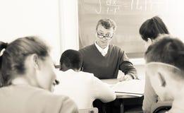Professorn som håller ögonen på som student, skriver av på examina royaltyfria bilder