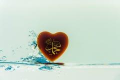 profeta del ` de Mohamed del ` del chapoteo del agua del símbolo del Islam con las burbujas del aire, en el fondo blanco fotos de archivo