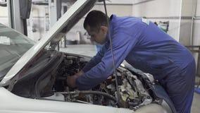 Proffesional在服务站的汽车维护 汽车服务、修理、维护和人概念-技工人 股票录像