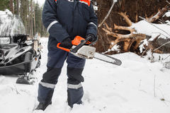 Proffesional Lumberjack hold hand saw. Winter wearing protection clothes using chainsaw. clean fallen trees Royalty Free Stock Photo