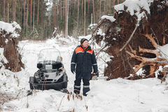 Proffesional Lumberjack hold hand saw. Winter wearing protection clothes using chainsaw. clean fallen trees Stock Images