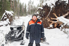 Proffesional Lumberjack hold hand saw. Winter wearing protection clothes using chainsaw. clean fallen trees Stock Photo