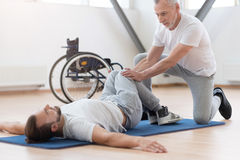 Proficient general practitioner stretching the disabled in the gym Stock Photos