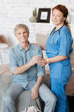 Proficient nurse providing medical assistance for elderly people royalty free stock photo