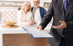 Proficient social security advisor demonstrating document for elderly couple Royalty Free Stock Photo