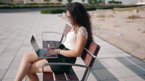 Profiel die van vrij Europese vrouwenzitting bij bank in openlucht, op laptop typen stock footage