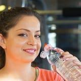 Profiel jonge donkerbruine vrouw die wat water van plastic fles na training gaan drinken stock fotografie