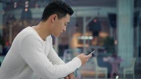 Profiel van Aziatisch mannetje met een telefoon in grote wandelgalerij stock footage
