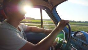 Profiel van de handen van de jonge mensenholding op stuurwiel en het drijven van een retro auto met zongloed bij achtergrond Kauk stock footage