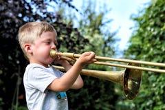 Profiel van de kleine jongen die trombone proberen te spelen royalty-vrije stock afbeeldingen