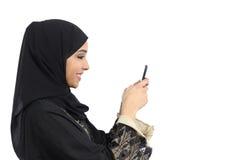 Profiel van een Arabische Saoedi-arabische vrouw die een slimme telefoon met behulp van Stock Foto