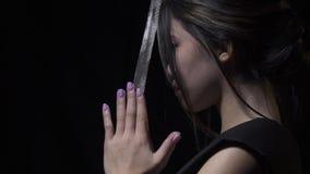 Profiel van een Aziatische vrouw met katana tussen haar palmen wordt geschoten die stock footage