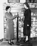 Profiel van een jonge vrouw in een eenvormig het meten gewicht van een andere jonge vrouw op een het wegen schaal (Alle afgeschil Royalty-vrije Stock Afbeelding