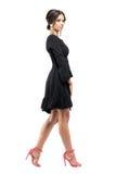 Profiel van elegante verfijnde vrouw in kleding en sandals die en camera lopen bekijken stock fotografie