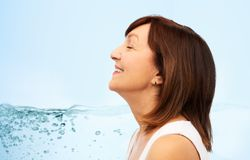 Profiel van glimlachende hogere vrouw over blauw water stock afbeelding