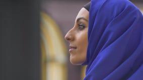 Profiel van jonge charmante moslimvrouw die in hijab met doordrongen neus zijdelings kijken stock videobeelden
