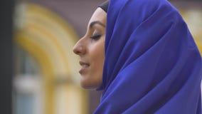 Profiel van jonge mooie moslimvrouw die in blauwe hijab met doordrongen neus zijdelings kijken stock videobeelden