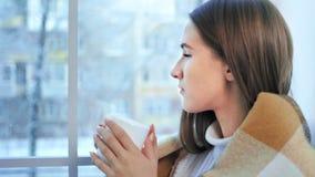 Profiel van jonge mooie vrouw die hete thee drinken en op venster de winterscène bekijken stock footage