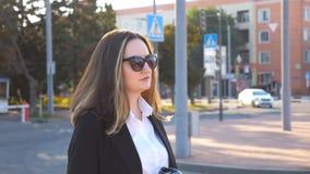 Profiel van jonge onderneemster die langs stedelijke straat in zonsondergangtijd lopen Bedrijfs vrouw die gaan werken Zeker meisj stock video