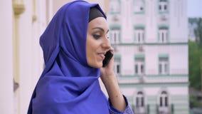 Profiel van jonge vrij moslimvrouw in hijab die op telefoon spreken en straat bekijken stock footage